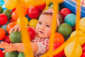 Toddler playing in indoor ball pit at a family-friendly play attraction