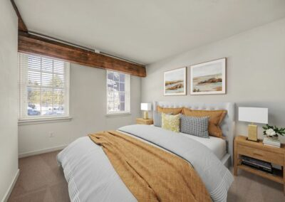 Model bedroom furnished with carpeted floors, large windows, king sized bed and 2 night stands.