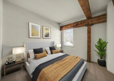 Model bedroom furnished with carpeted floors and wooden beam architecture, with a bed and 2 nightstands in West Chester, PA