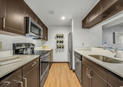 Model kitchen with spacious counters, breakfast bar and modern stainless steel appliances at Sharples Works Apartments in West Chester, PA.