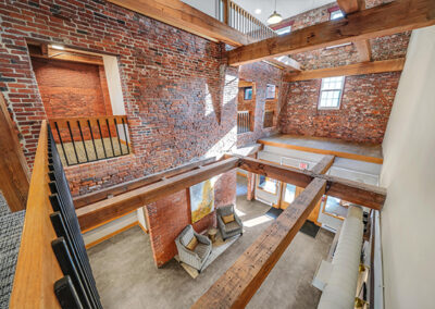 Resident lounge with exposed brick walls and beamed ceiling at Sharples Works' luxury apartments in West Chester.