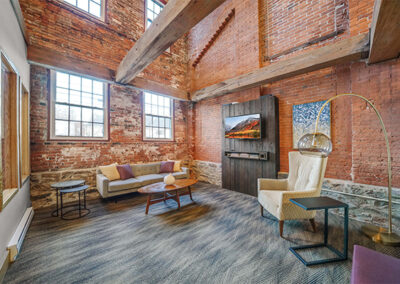 Resident lounge with exposed brick walls and beamed ceiling furnished with couches and chairs at Sharples Works apartments in West Chester.